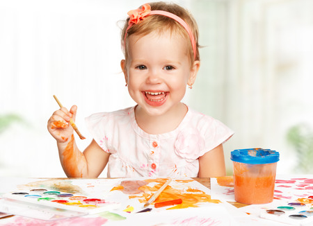 art and craft: happy baby child girl draws paints