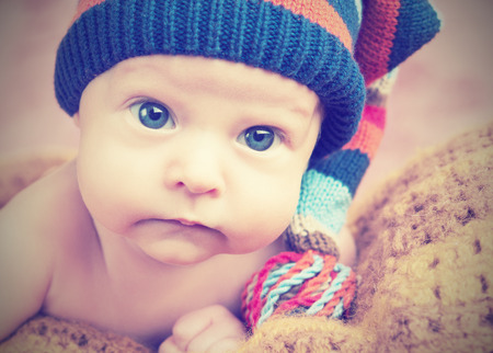 cute happy newborn baby in knitted hat cap photo