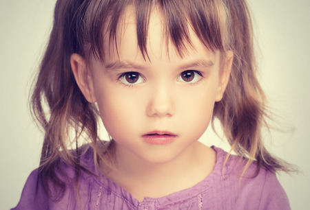 face of a little beautiful girl with sad eyes Imagens