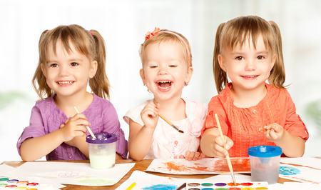 school activities: happy sister little girl in kindergarten draw paints