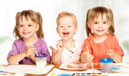 infant: hermana peque�a ni�a feliz en las pinturas del drenaje de jard�n de infantes