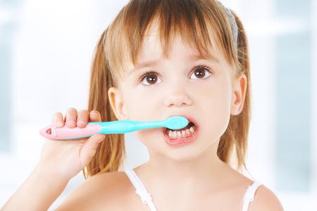 dental hygiene. happy little girl brushing her teeth Imagens