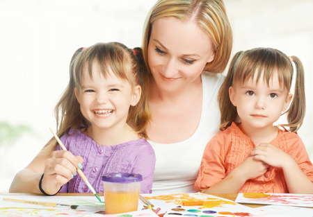 children little twin sisters draw paints with her mother in kindergarten on a white background photo