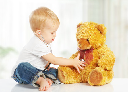 cute baby plays in doctor toy teddy bear and stethoscope Stock Photo