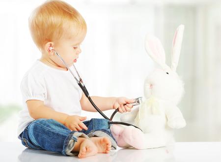 persona malata: cute baby gioca nel medico coniglio giocattolo coniglio e stetoscopio