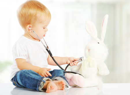 cute baby plays in doctor toy bunny rabbit and stethoscope