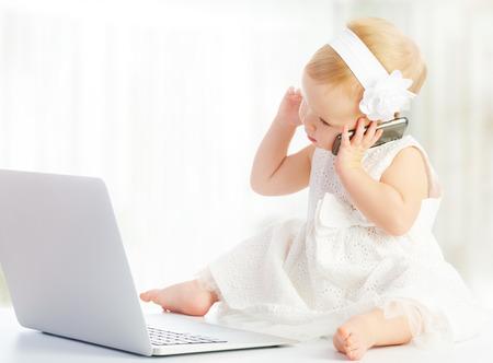 conversa: ni�a en un ordenador port�til, tel�fono m�vil Foto de archivo