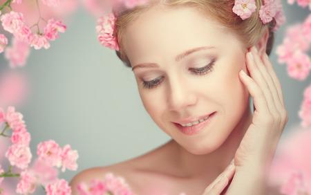 그녀의 머리에 분홍색 꽃과 아름 다운 젊은 여자의 아름다움 얼굴