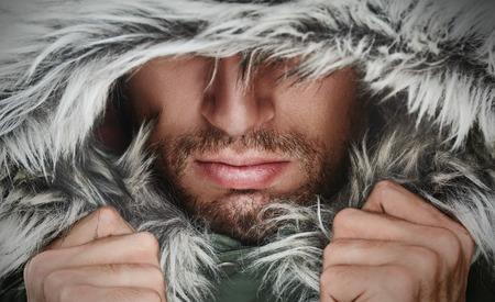 brutale gezicht van een man met baard haren en capuchon winter