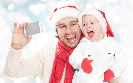 selfe  in winter. happy family father dad playing with baby daughter and photographed on a mobile phone photo