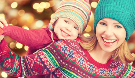 happy family mother and baby little daughter playing in the winter for the Christmas holidays photo