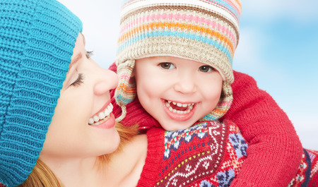 winter woman: happy family mother and baby little daughter playing in winter in warm sweaters and hats