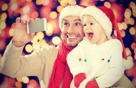 Selfe in kerst. gelukkig gezin papa met dochter en gefotografeerd op de mobiele telefoon