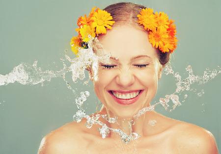 schoonheid gelukkig lachend meisje met spatten van water en gele bloemen