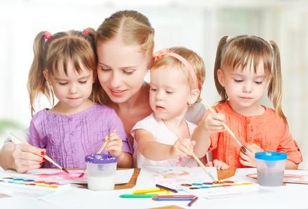 tutor: niños hermanitas gemelas drenan las pinturas con su madre en el jardín de infantes