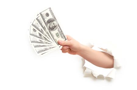 dollaro: mano umana con denaro dollari americani attraverso un buco nella carta per manifesti bianca Archivio Fotografico