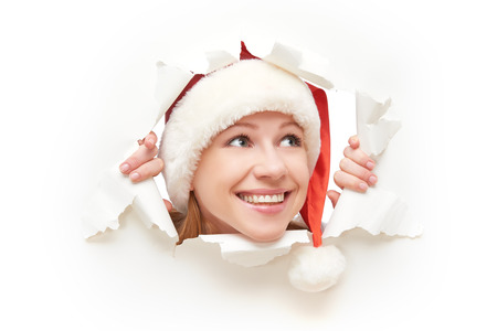 face of  happy woman with christmas hat peeking through a  hole torn in white paper poster photo