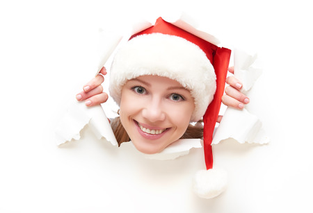 broken through: face of  happy woman with christmas hat peeking through a  hole torn in white paper poster Stock Photo