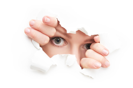 peek: eyes of a young curious woman peeking through a  hole torn in white paper poster Stock Photo