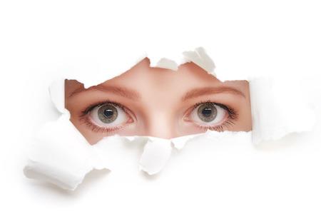 흰 종이 포스터에서 찢어진 구멍을 통해 엿보기 젊은 호기심 여자의 눈