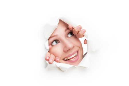 broken through: face of a young curious woman peeking through a  hole torn in white paper poster