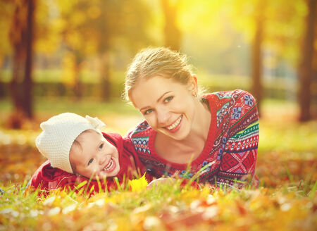 female child: happy family: mother and child little daughter playing and laughing in the autumn on the nature walk outdoors Stock Photo