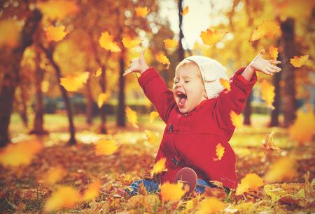 szczęśliwy małe dziecko, dziewczynka śmiejąc się i grać jesienią na spacerze przyrody w plenerze