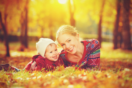 happy family: mother and child little daughter playing and laughing in the autumn on the nature walk outdoors photo