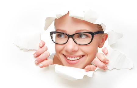 Cara de una joven curiosa con gafas mirando a través de un agujero rasgado en un cartel de papel blanco