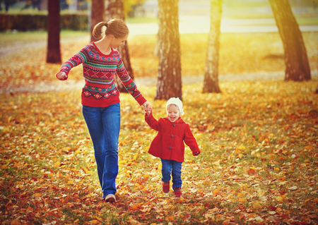 fall fun: happy family mother and child little daughter running and playing on autumn walk
