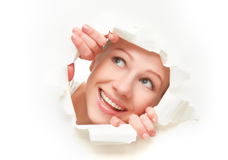 face of a young curious woman peeking through a  hole torn in white paper poster photo