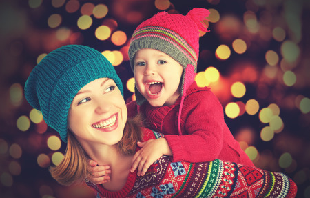 sueteres: madre de familia feliz y pequeña hija bebé jugando en el invierno para las vacaciones de Navidad Foto de archivo