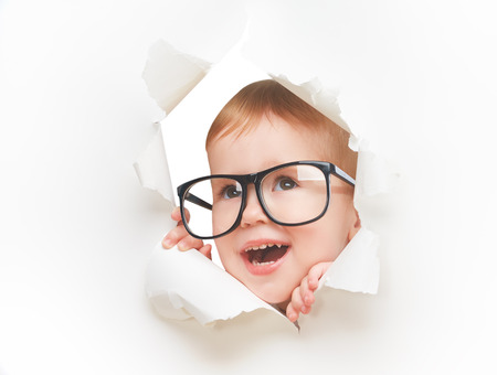 Funny child  baby girl with glasses peeping through a hole in an empty white paper poster Foto de archivo