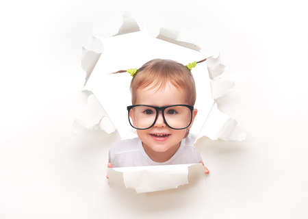 child baby girl with funny tails with glasses peeping through a hole in an empty white paper poster photo