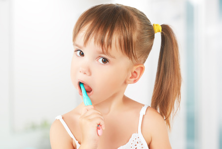 cleanliness: dental hygiene. happy little girl brushing her teeth Stock Photo