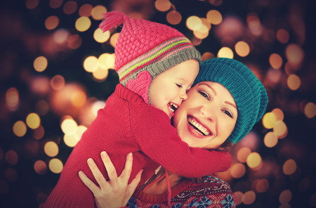 familia feliz: madre de familia feliz y pequeña hija bebé que juega en el invierno para las vacaciones de Navidad