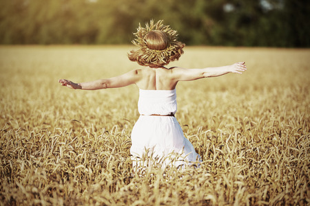hair back: happy girl enjoying life and freedom in wheat field in summer
