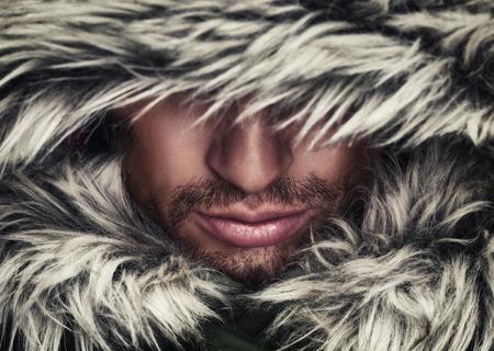 ropa invierno: cara brutal de un hombre con barba y pelos de invierno con capucha
