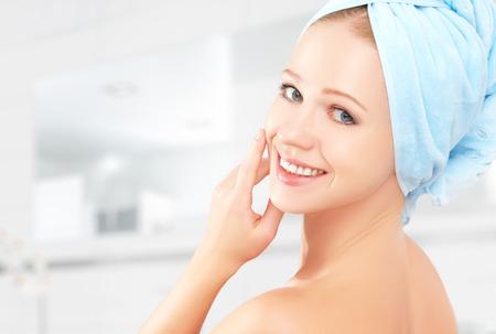 masaje facial: protecci�n de la piel. joven sana hermosa en una toalla en el ba�o