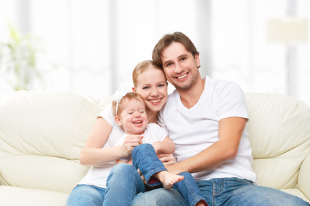 Happy family mother, father, child baby daughter at home on the sofa playing and laughing photo