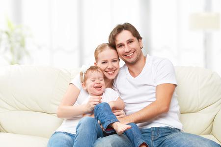 dadã  daughter: Madre de familia feliz, padre, hijo hija bebé en casa en el sofá jugando y riendo Foto de archivo