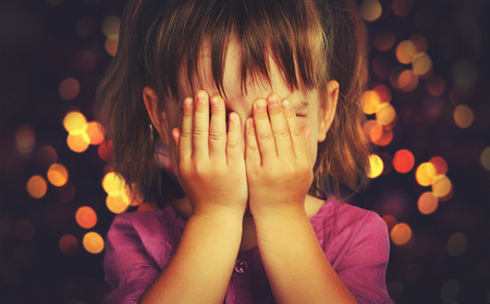 the anticipation: little girl closed eyes  her hands in anticipation of a Christmas miracle and a gift Stock Photo