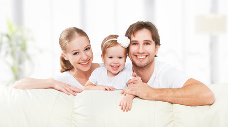 Happy family mother, father, child baby daughter at home on the sofa playing and laughing Banque d'images