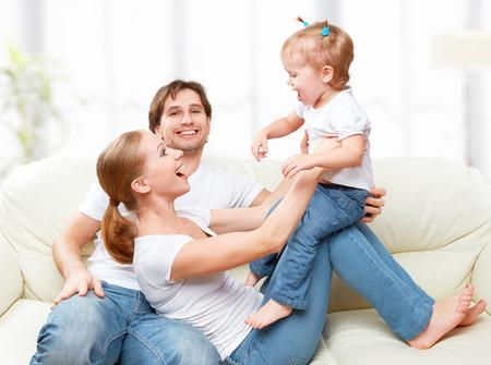 Gelukkig gezin moeder, vader, kind dochtertje thuis op de bank spelen en lachen