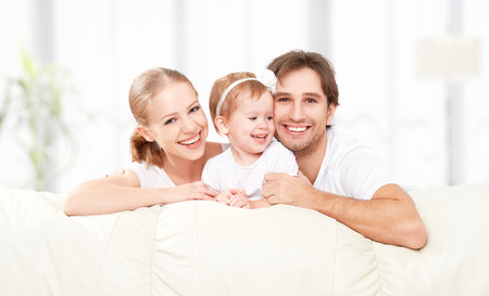 Happy family mother, father, child baby daughter at home on the sofa playing and laughing Stock Photo