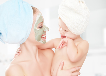 salon and spa: family beauty treatment in the bathroom. mother and daughter baby girl make a mask for a face skin