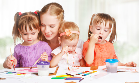 children little twin sisters draw paints with her mother in kindergarten