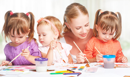 preschool children: children little twin sisters draw paints with her mother in kindergarten
