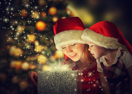 il natale: Scatola magica del regalo di Natale e una donna felice famiglia madre e figlia neonata