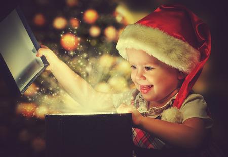 クリスマスの奇跡、魔法のギフト用の箱および女の子の赤ちゃん 写真素材